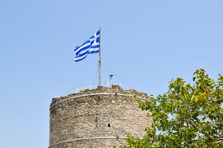 Flag on Kavala ancient tower in Greece.