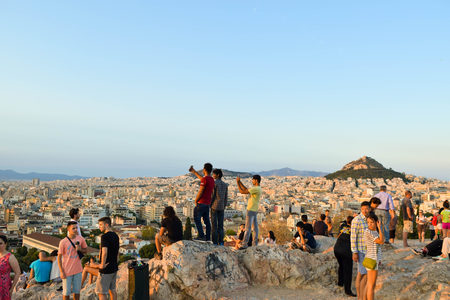 Athens, Greece - July 15, 2017: Tourists on the Areopagus Hill admire the cityscape of Athens at sunset. 新聞圖片