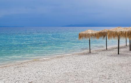 Blue clouds on the horizon and sunny beach of Kineta, Greece. Stock Photo