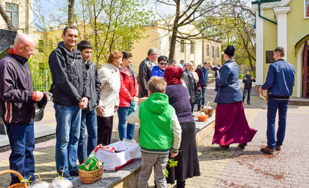 Kiev, Ukraine - April 16, 2017: The priest during Easter consecration of eating and parishioners holy water. Editorial