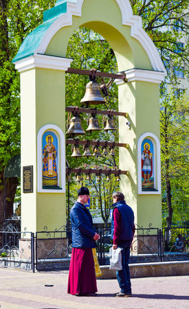 Kiev, Ukraine - April 16, 2017: The priest converses with a parishioner near a small bell tower. Banque d'images - 101834424
