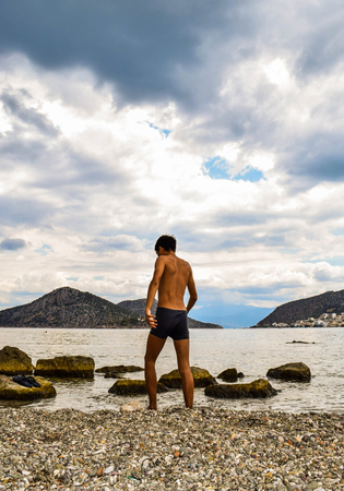 The teenager explores the small beach of Asini, Greece.