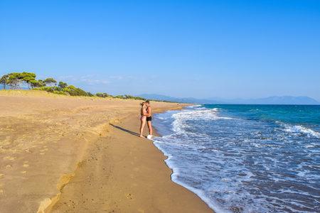 The couple on the beautiful sandy Kaifas beach, Greece.