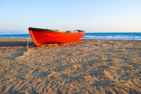 The small boat on the deserted sandy Kaifas beach at sunset, Greece. Stock Photo