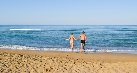 The young couple runs to plunge into the sea. Zacharo beach, Greece.