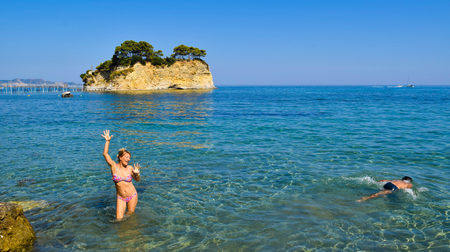 Dancing girl on the background of little island Cameo, Zakynthos, Greece.