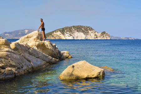 The man on the rock in sea. Marathias beach, Zakynthos Island, Greece.