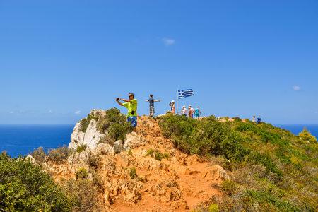 Shipwreck Bay, Zakynthos Island, Greece - July 26, 2017: Tourists on the cape photograph the Shipwreck Beach.
