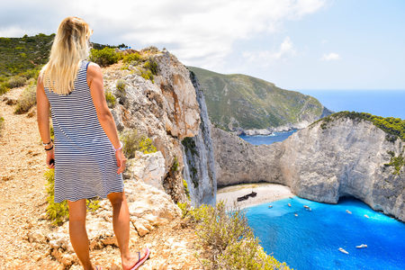The girl on the edge of the cliff in the background of Shipwreck Bay, Zakynthos Island, Greece.