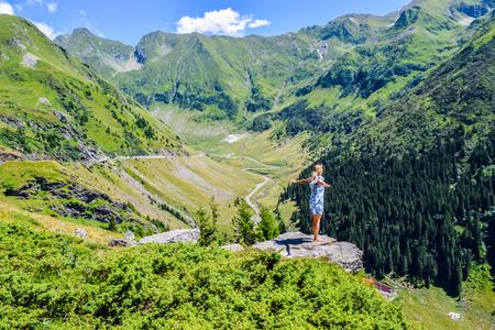 Girl on the cliff edge near Transfegerasan mountain road.