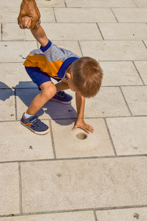 Zadar, Croatia - July 6, 2018: Child listen music of the Sea Organ on the promenade. Редакционное