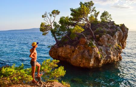 The guy at sunset near the rock Brela. Punta Rata Beach, Croatia.
