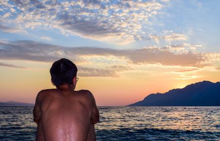 The guy on the background of beautiful sunset over the sea. Punta Rata Beach, Brela, Croatia.
