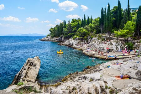 Trpanj, Peljesac peninsula, Croatia - July 24, Croatia: Vacationers on a rocky beach.