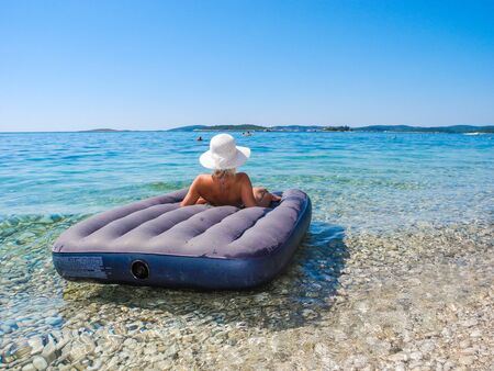 Girl on a mattress during beach vacations.