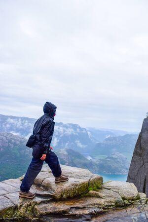 Chica en Prekestolen o Pulpit Rock bajo la lluvia. Noruega.