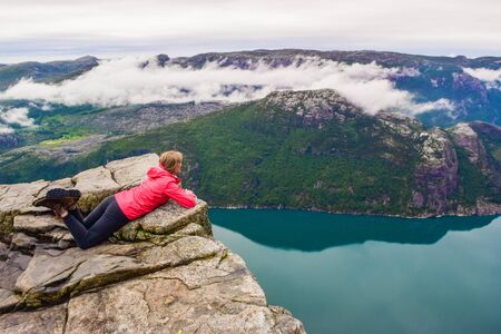 The girl lying on Prekestolen looks down at Lucefjord. Pulpit Rock. Norway. Banco de Imagens