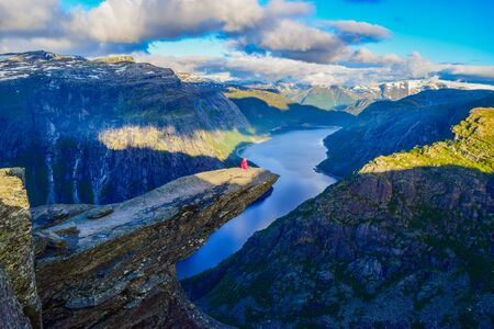 The girl sits on the edge of the cliff on the Trolltunga, Norway.