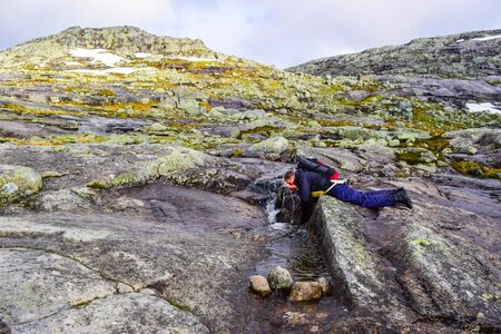 The tourist drinks clean water from the stream along a road to Trolltunga, Norway.
