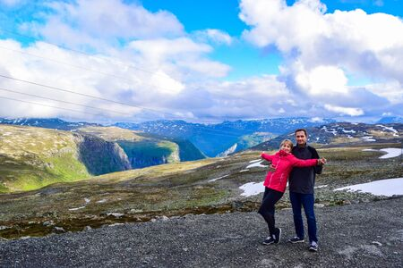 Couple of tourists near national tourist snow road Aurlandsvegen (f243) hat is runs across the mountains. Norway.