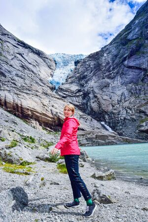 The young woman near the Brikdalsbreen glacier, which is the sleeve of large Jostedalsbreen glacier. Melting glacier forms the Briksdalsbrevatnet lake with clear water. Norway.
