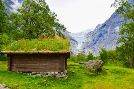 Traditional houses with green grass on the roof against the background of the Brikdalsbreen glacier which is the sleeve of large Jostedalsbreen glacier. Norway.