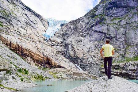 The man near the Brikdalsbreen glacier, which is the sleeve of large Jostedalsbreen glacier. Melting glacier forms the Briksdalsbrevatnet lake with clear water. Norway.