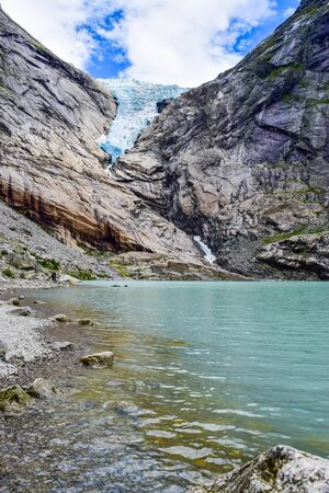 The Brikdalsbreen glacier, which is the sleeve of the large Jostedalsbreen glacier in Norway. The melting glacier forms the Briksdalsbrevatnet lake with clear water.