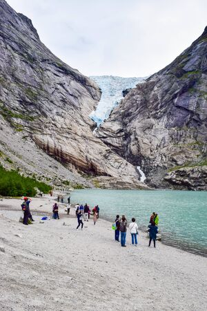 Brikdalsbre, Norway - June 25, 2019: Tourists near the Brikdalsbreen glacier, which is the sleeve of large Jostedalsbreen glacier. Melting glacier forms the Briksdalsbrevatnet lake with clear water. N