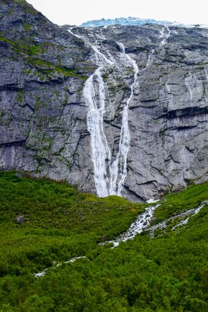 Waterfall and river which is located near path to the Briksdalsbreen (Briksdal) glacier. The melting of this glacier forms waterfall and river with clear water. Jostedalsbreen National Park. Norway. 写真素材