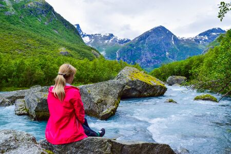 The young woman near river which is located near path to the Briksdalsbreen (Briksdal) glacier. The melting of this glacier forms waterfall and river with clear water. Jostedalsbreen National Park. No