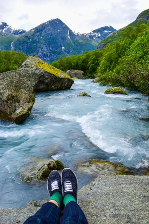 Tourists legs above river which is located near path to Briksdalsbreen (Briksdal) glacier. The melting of this glacier forms waterfall and river with clear water. Jostedalsbreen National Park. Norway 写真素材