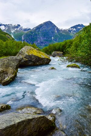 River which is located near path to the Briksdalsbreen (Briksdal) glacier. The melting of this glacier forms waterfall and river with clear water. Jostedalsbreen National Park. Norway.