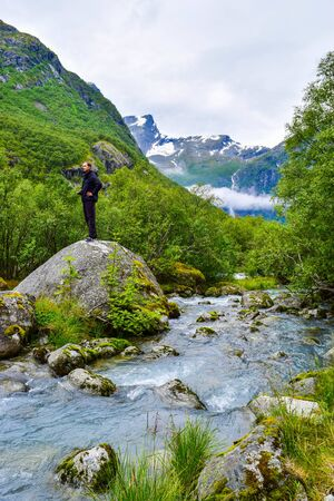 Tourist near river which is located near path to the Briksdalsbreen (Briksdal) glacier. The melting of this glacier forms waterfall and river with clear water. Jostedalsbreen National Park. Norway.