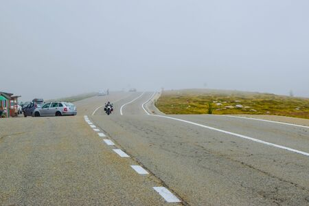 Motorcyclist and cars in fog on the Transalpina road DN67C. This is one of the most beautiful alpine routes in Romania and the highest mountain asphalt road in Romania and  Carpathians mountains.