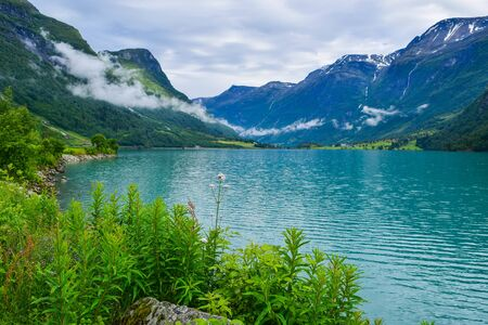 Landscape of beautiful Oldevatnet glacial lake and foggy mountains in which there are glaciers of Jostedalsbreen National Park. Norway.