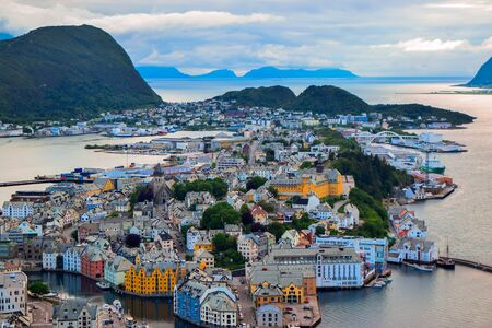The amazing sunset over Alesund cityscape. Neoclassical and neo-Gothic stone buildings. Art Nouveau architecture. Sun rays illuminate Atlantic Ocean and islands. View from Aksla viewpoint. Norway.