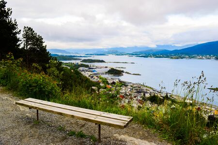 Bench on the mountain Aksla at the Alesund cityscape background whit architecture of city in Art Nouveau, Neoclassical and neo-Gothic  style. Sun rays illuminate Atlantic Ocean and islands. Norway.