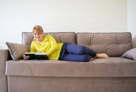 Caucasian woman is reading a book lying at home on the comfortable sofa ones during quarantine and social distance at Coronovirus (COVID-19) pandemic. Home leisure. It's good to be home.