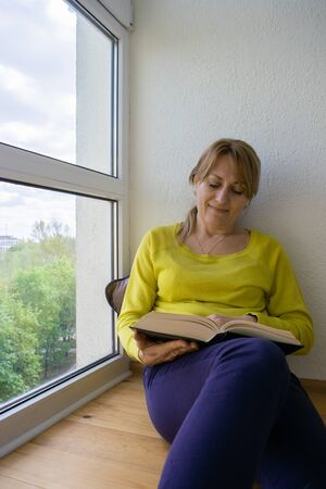 Caucasian woman is reading a book sitting at home near the panoramic window during a period of quarantine. Social distance during an COVID-19 pandemic. Home leisure. It's good to be home.