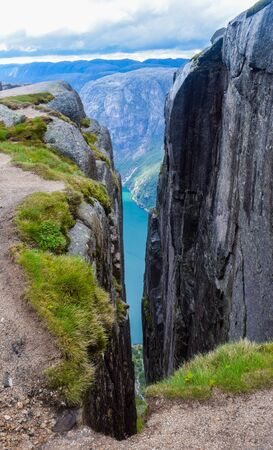 View of Lysefjorden through a crevice between two cliffs 984 meters high, where the famous Kjeragbolten stuck nearby - the most dangerous stone in the world. Mountain Kjerag, Rogaland county, Norway.