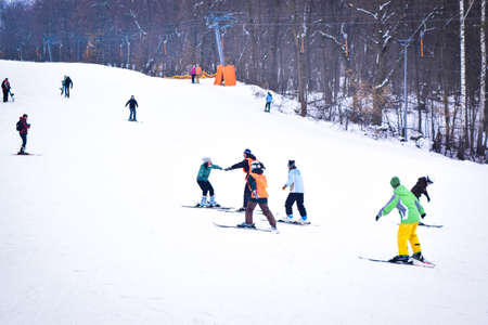 Kiev, Ukraine - February 18, 2018: Skiers on a snow slide with a ski lift. Teaching with an instructor teaching skiing. Winter fun. Skiing on the ski slope. Éditoriale