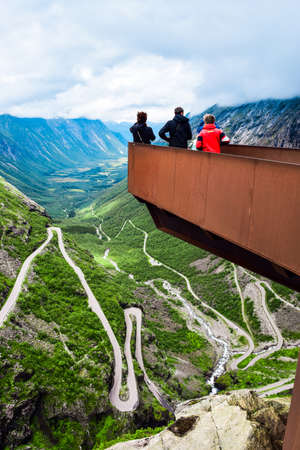 Tourists on the viewpoint over Trollstigen or Troll Stairs, a serpentine mountain road that is popular tourist attraction due to its eleven hairpin bends up mountainside. More og Romsdal, Norway.