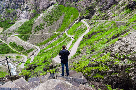 Man tourist on the steps of hiking trail near Trollstigen or Troll Stairs, a serpentine mountain road that is popular tourist attraction due to its eleven hairpin bends up mountainside. Norway.