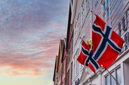 Norwegian flags waving in the wind on the wall of an old wooden house in Bergen against a beautiful sky at sunset. Bergen is a city and municipality in Vestland county on the west coast of Norway.