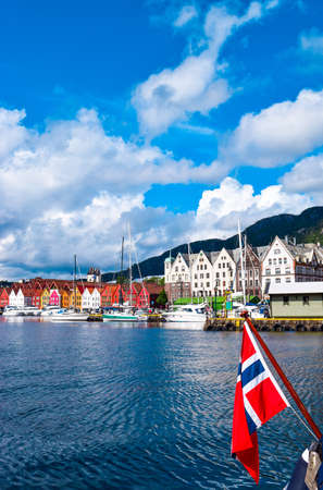 Norwegian flag on the background of the bay and the old wooden houses on the waterfront of Bergen. Bergen is a city and municipality in Vestland county on the west coast of Norway.