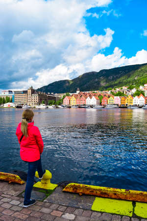 Girl tourist on the background of the sea bay and old wooden houses on the embankment of Bergen. Bergen is a city and municipality in Vestland county on the west coast of Norway. 免版税图像
