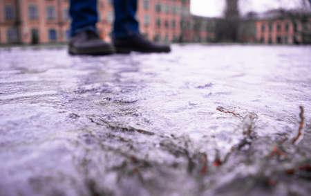 Sidewalk covered with slippery ice against the background of pedestrian feet and city buildings. Sharp drop in temperature froze raindrops, covering everything with slippery ice. Selective focus. 免版税图像