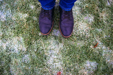 Legs in boots against the background of frozen lawn covered with ice with green grass. Winter weather surprises. Sharp drop in temperature froze raindrops, covering everything with slippery ice. 免版税图像