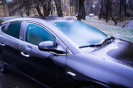 The parked car is covered with a crust of transparent ice. Winter weather surprises. The sharp drop in temperature froze the raindrops, covering everything with slippery ice.